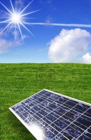 Foto de Panel de energía solar contra cielo azul y hierba - Imagen libre de derechos