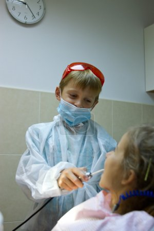 couple of kids playing doctor at the dentist