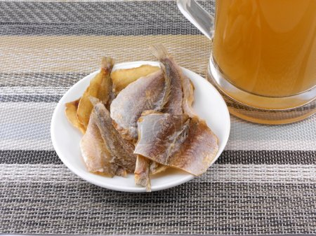 smoked fish and cup of beer on a background