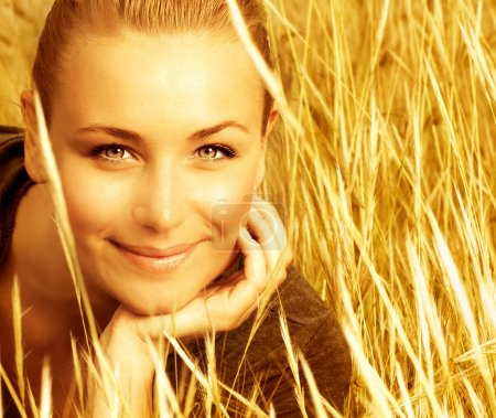 Photo for Picture of attractive smiling girl sitting in golden wheat field, closeup portrait of beautiful young blond female on yellow ryes background, enjoying countryside, a - Royalty Free Image