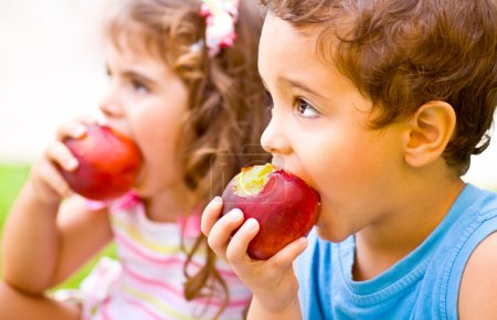 Photo for Photo of two happy children eating apples, brother and sister having picnic outdoors, cheerful kids biting red ripe peach, adorable infant holding fresh fruits in ha - Royalty Free Image