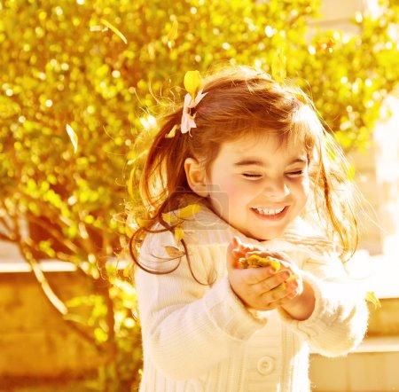 Photo pour Photo de jolie petite fille heureuse profitant de la nature automnale dans le parc, mignon enfant joyeux jouant avec des feuilles d'or dans la forêt sèche, brune petite fille avec fermé - image libre de droit