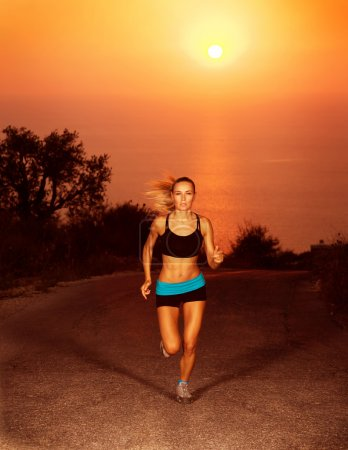 Photo for Image of of sporty blond female running along the road over sunset, slim athletic woman run in marathon, active girl doing fitness exercise outdoors, weight loss, bo - Royalty Free Image