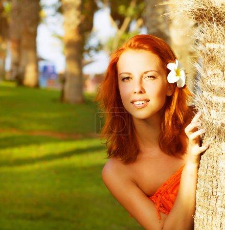 Photo pour Photo de peek de jolie fille dehors derrière un palmier, le portrait agrandi de belle femelle avec la fleur de frangipanier dans les cheveux roux, femme romantique, appréciant la belle n tropical - image libre de droit