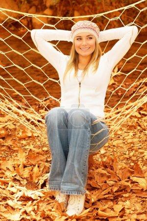 Photo pour Photo de jolie fille balançant dans l'hamac sur le jardin arrière-cour, mignonne femme portant un chapeau élégant chaud, belle fille blonde s'amusant dans le parc d'automne, insouciante et libérée - image libre de droit