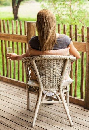 Rear view of girl sitting on veranda