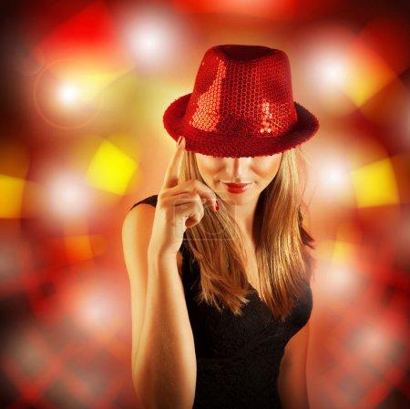 Photo pour Photo de femme blonde port élégant chapeau rouge brillant, fille chanteuse glamour avec le doigt vers le haut isolé sur flou fond de lumières, célébration du nouvel an, Noël, vie nocturne, partie de club de danse - image libre de droit