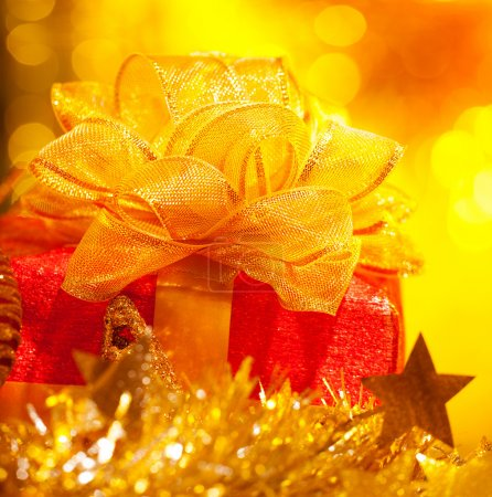 Photo for Photo of Christmas present, red gift box with big golden bow on yellow blur background, Chritmastime holiday, star decoration, New Year party, luxury ornament, beautiful greeting card - Royalty Free Image