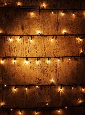 Foto de Foto de puerta decorada, antecedentes, pared arbolado vintage con brillantes luces brillantes de la Navidad, guirnalda decorativa, adorno festivo eléctrico, año nuevo iluminado ornamento casero - Imagen libre de derechos