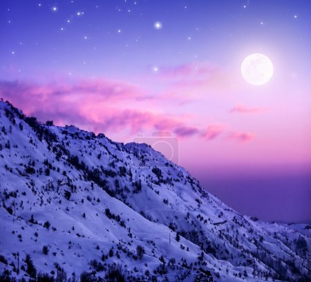Photo for Photo of beautiful snowy mountains on purple sunset background, Faraya mountain in Lebanon covered with white snow, wintertime cold weather, moonlight in dark night, winter holidays concept - Royalty Free Image