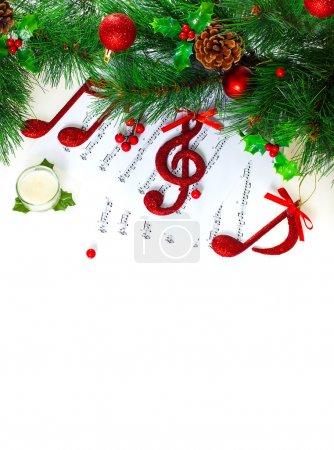 Photo pour Photo de symbole musical de Noël clé de sol, rouge sur note pages, frontière de vacances festives, chant traditionnel de Noël, nouvel an des arbres décorés avec différentes belles boules, carte de voeux de Noël - image libre de droit