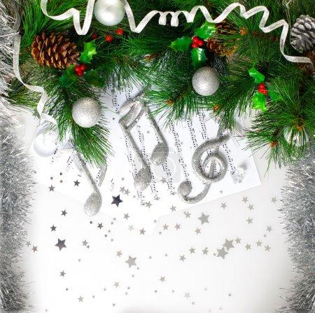 Photo pour Photo de symbole musical de Noël, branche de l'arbre de Noël vert décoré, brillant argent clef triple page note, boules festives et cône accrocher sur le sapin, mélodie de carol de Noël traditionnelle - image libre de droit