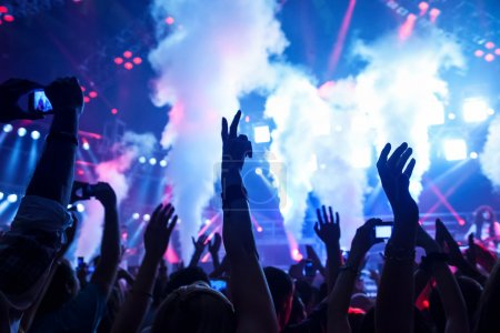 Photo for Picture of rock concert, music festival, New Year eve celebration, party in nightclub, dance floor, disco club, many standing with raised hands up and clapping, happiness and night life concept - Royalty Free Image