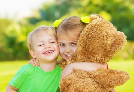 Photo for Photo two cute child hugging outdoors, brother and sister having fun on backyard in spring, nice little girl with adorable boy playing with big soft bear toy, best friends, happy childhood concept - Royalty Free Image
