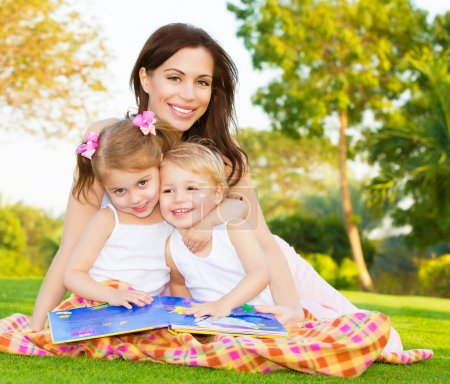 Photo for Picture of young happy family, beautiful mother with two cute kids having fun outdoors in spring, pretty female with son and daughter sitting down on green meadow on backyard, daycare concept - Royalty Free Image