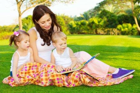 Photo pour Photo de jeune mère avec deux enfants mignons lisant le livre à l'extérieur au printemps, maman heureuse enseignant à ses enfants dans le parc, garderie, belle femme avec fils et fille s'amusant sur la cour - image libre de droit