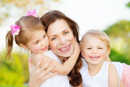 Photo for Picture of young mother hugging two little children, closeup portrait of happy family, cute brunette female with daughter and son outdoor in spring time, smiling faces, happiness and love concept - Royalty Free Image