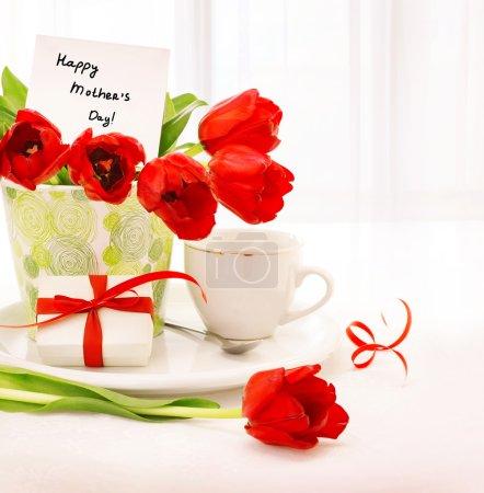 Photo pour Photo du pot de belles tulipes avec boîte-cadeau et tasse de thé sur la table à la maison, le petit déjeuner pour maman, heureuse fête des mères, boisson du matin, romantique, nature morte, décoration intérieure, fleurs rouges fraîches - image libre de droit
