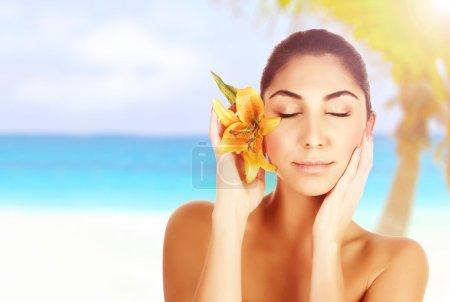 Photo pour Photo de belle femme sur la plage avec fleur de lys jaune à la tête, femelle arabe aux yeux fermés bénéficiant d'un spa de jour, d'un traitement de beauté, de soins du corps, d'une station tropicale de luxe, de vacances et d'une concession de voyage - image libre de droit