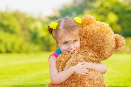 Photo pour Jolie fille jouant avec peluche extérieure, mignon infantile s'amuser sur l'arrière-cour au printemps temps, notion d'enfance heureuse - image libre de droit