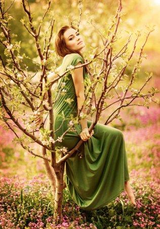 Photo pour Nymphe de la forêt des fées-queue, belle femme sexy au jardin printanier, vêtue d'une robe longue, séance sur l'arbre fleurissant, style vintage fashion rêveuse - image libre de droit