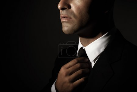 Photo for Young handsome man fixed tie isolated on black background, face part, successful businessman, mens fashion, glamour concept - Royalty Free Image