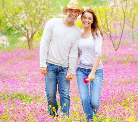 Photo pour Bonne amie et son copain main dans la main et la marche sur terrain floral rose, famille jouissant, notion de relation amoureuse - image libre de droit