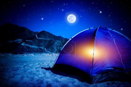 Photo pour Camp sur la plage de sable, tente la nuit avec lumière à l'intérieur, lumière de la lune, tourisme actif, randonnée et concept de voyage - image libre de droit