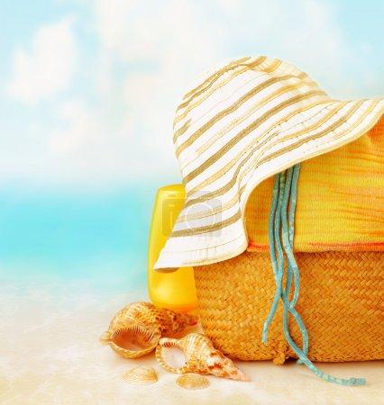 Photo pour Accessoires de plage sur le sable près de la mer, protection de la peau, coquillage, chapeau, sac, spa de jour, station tropicale, mode de vie de luxe, vacances d'été - image libre de droit