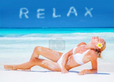 Photo pour Fille se détendre sur la plage avec des fleurs frangipani fraîches en cheveux blonds, prendre un bain de soleil, détente sur la station thermale de luxe, concept de vacances d'été - image libre de droit