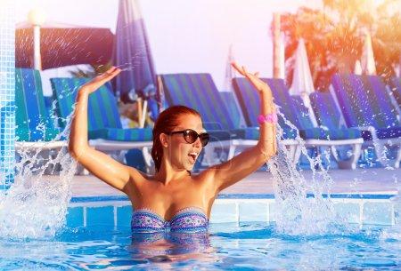 Photo pour Heureuse jolie fille ayant plaisir dans la piscine, mignon ludique éclaboussures femelle d'eau dans la piscine, détente et jouer au bord de la piscine, concept de vacances d'été - image libre de droit