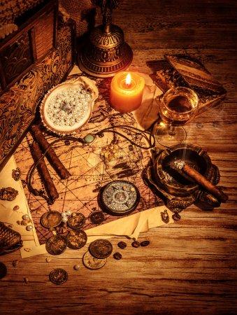 Photo pour Frontière de trésors anciens, pirates butin nature morte sur table en bois, boussole et carte, pièces d'or et notion de médaillon, aventure et picois âgée - image libre de droit