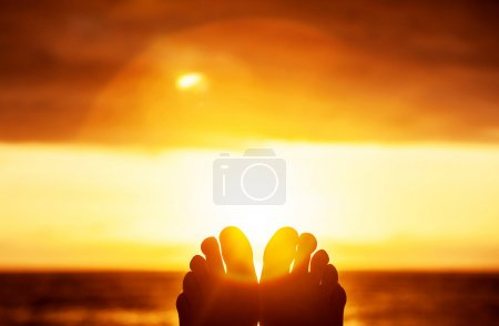 Photo for Peaceful beautiful orange sunset, body part, persons toes, carefree lifestyle, summer vacation, harmony and freedom concept - Royalty Free Image