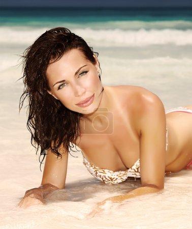 Photo pour Femme brune sensuelle prend le bain de soleil au bord de mer, à la mode sexy modèle allongé sur la plage de sable blanche propre, photo de style rétro, concept de vacances d'été chaud - image libre de droit