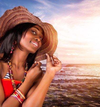 Photo pour Gros plan portrait de belle femme africaine sur la plage, modèle sexy posant sur le bord de mer au coucher du soleil, portant un chapeau élégant et des accessoires à la mode, vacances d'été - image libre de droit