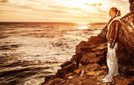 Photo pour Fille mignonne touristiques bénéficiant d'une lumière chaude du coucher du soleil sur la falaise, voyager en Afrique du Sud, concept de mode de vie, de voyages et de tourisme aventure - image libre de droit