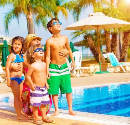 Photo pour Héhé mignon s'amuser près de piscine sur luxury resort tropical, mère avec enfants regardant vers le haut dans le ciel, vacances d'été, notion de l'amour - image libre de droit