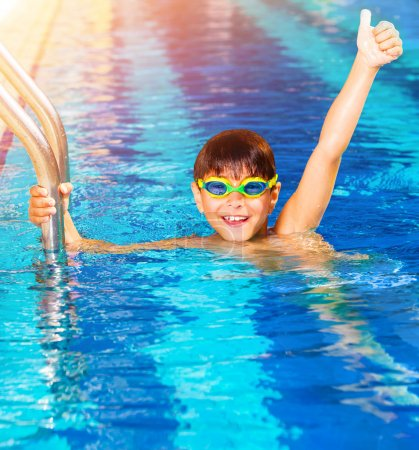 Photo for Closeup on little boy wearing swimming goggles in the pool, junior swimming competition, happy winner with raised up hand, summer time sport - Royalty Free Image