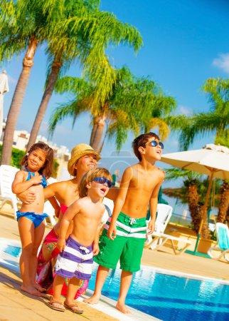Photo pour Mignon grande famille debout près de bord de la piscine et regardez dans le ciel, profitant des vacances d'été, expression du visage, détente sur le concept de plage, amour et amitié - image libre de droit