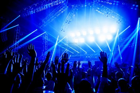Photo for Rock concert, crowd of young people enjoying night performance, raised up and clapping hands, dance club, bright blue lights, music entertainment - Royalty Free Image