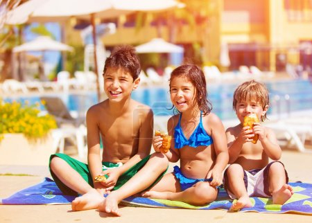 Photo for Three kids sitting down and eating croissant near pool, picnic outdoors, beach resort, summer vacation, happy childhood concept - Royalty Free Image