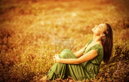 Photo for Romantic woman wearing long elegant dress sitting on golden dry field, autumn season, relaxation in countryside, enjoying nature, pleasure concept - Royalty Free Image