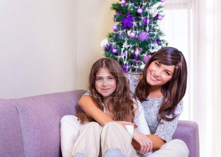 Photo pour Joyeuse mère et fille, assis sur le canapé près de bel arbre de Noël décoré, passer le nouvel an à la maison ensemble, le concept de famille heureux - image libre de droit