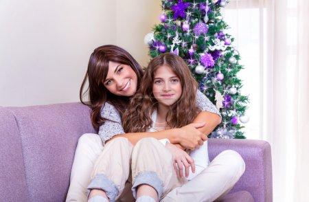 Photo pour Joyeux jeune femme avec jolie fille adolescente assise sur un canapé à la maison, profitant de la famille, décoration de Noël traditionnelle, concept de vacances du Nouvel An - image libre de droit