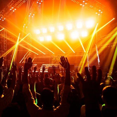 Photo pour Photo de jeunes gens s'amuser au concert de rock, style de vie actif, applaudissant à bande de la célèbre musique, vie nocturne, dj sur la scène dans le club, danser sur le dancefloor, nuit perfomance foule de fans - image libre de droit