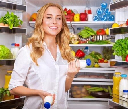 Woman chosen yogurt in opened refrigerator