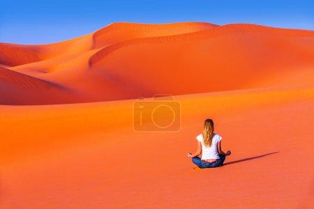 Photo pour Méditation dans le désert, une vie active saine, jeune femelle assis seul sur le sable chaud orange, équilibre zen, magnifique concept de nature, de paix et de détente - image libre de droit