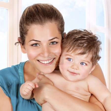 Happy mother and baby boy enjoying time at home, h...