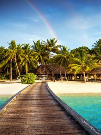 Photo for Wooden bridge to island beach resort, beautiful colorful rainbow over fresh green palm trees, luxury hotel on Maldives island, summer vacation concept - Royalty Free Image