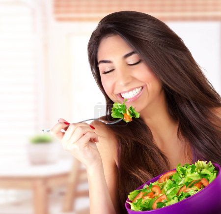Cute girl eating salad